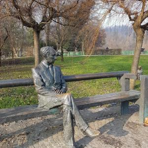Statue of Edvard Kocbek, in Tivoli Park with view of Ljubljana